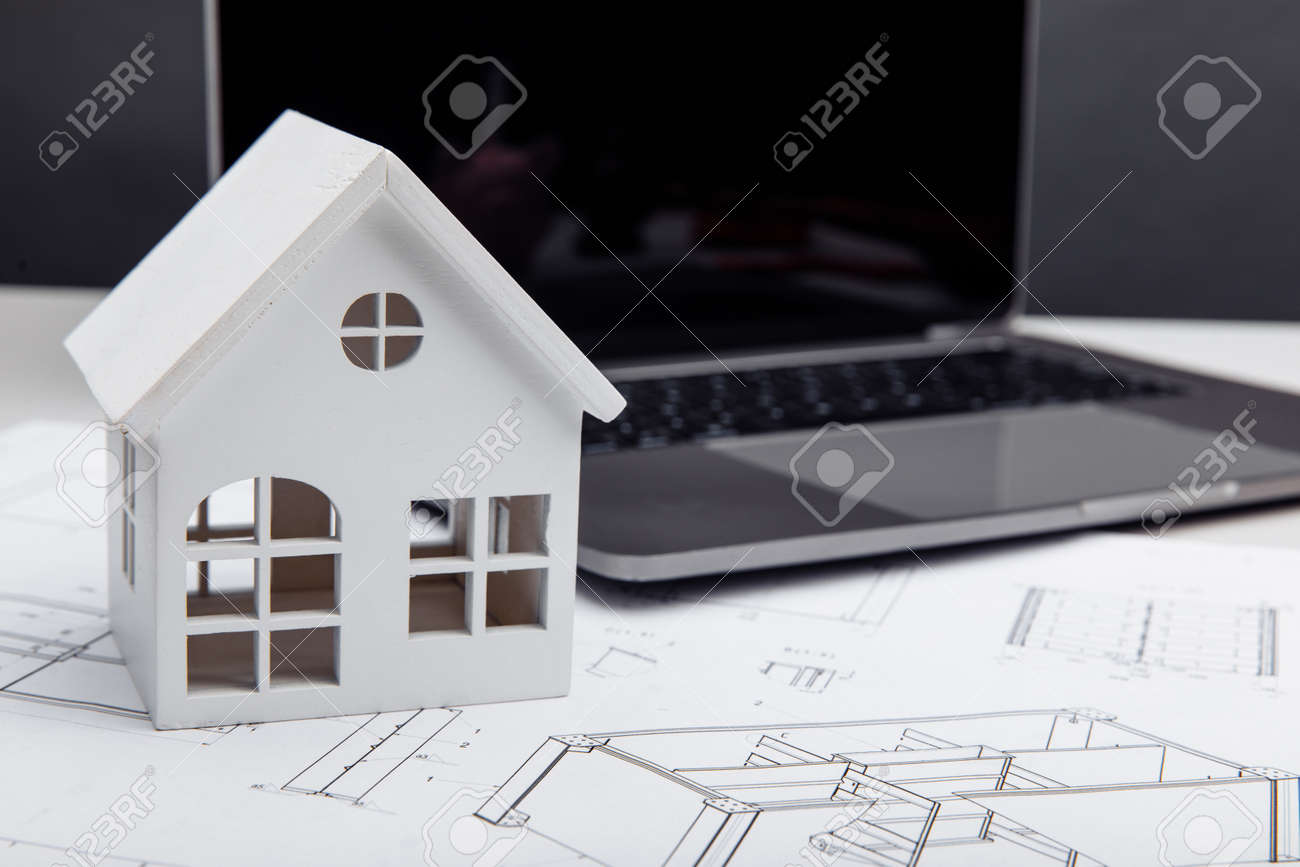 Model of house on drawing and laptop. Building and architect concept - 172813876