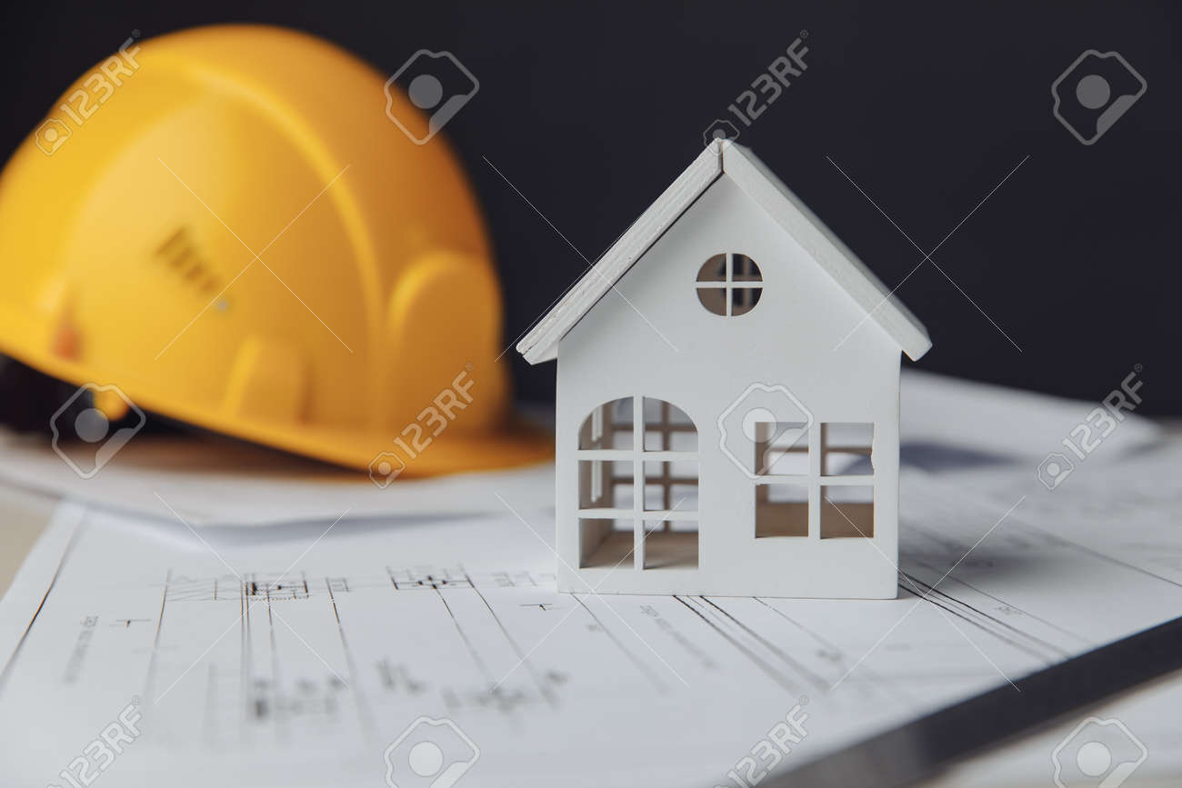 Construction plans with yellow helmet and white house on a table - 172814173