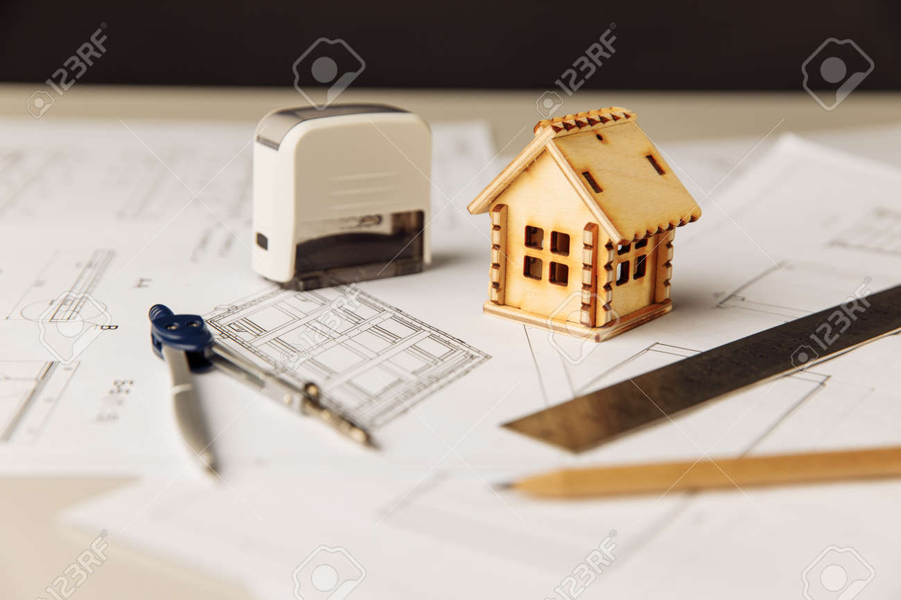 Blueprint with wooden house, drawing tools and glasses on a table - 172813862