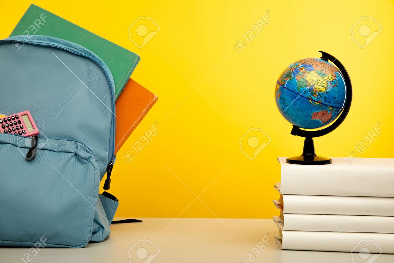 Blue backpack with school supplies with globe on books. Back to school concept - 172813656