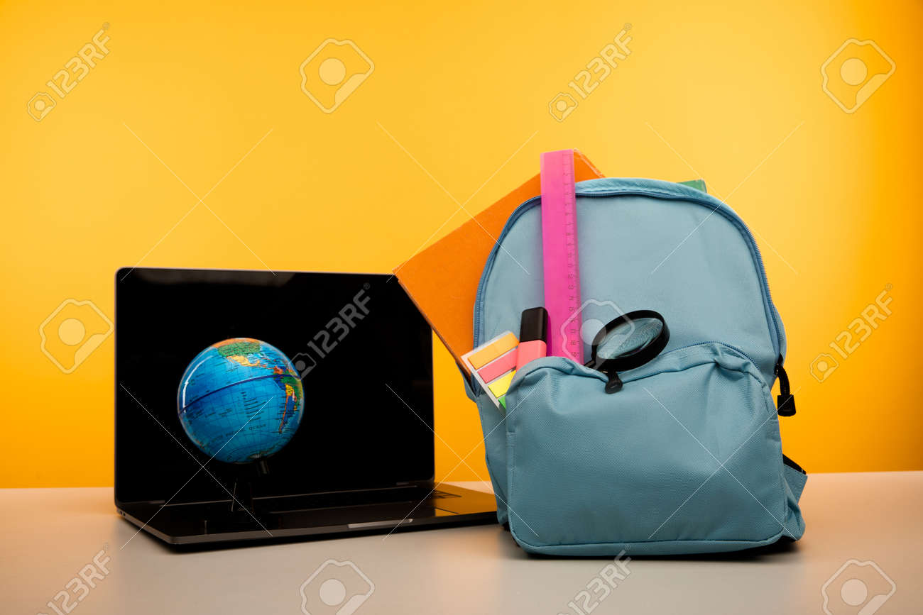 School backpack with supplies and laptop on a table. Online education concept - 172814167