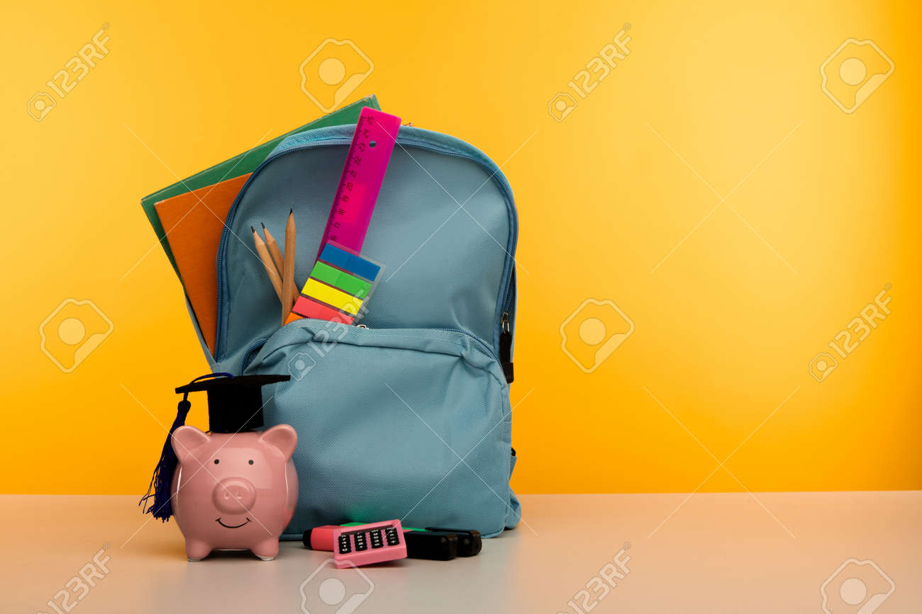 Blue backpack with school tools and piggy bank in hat on yellow background - 172815062