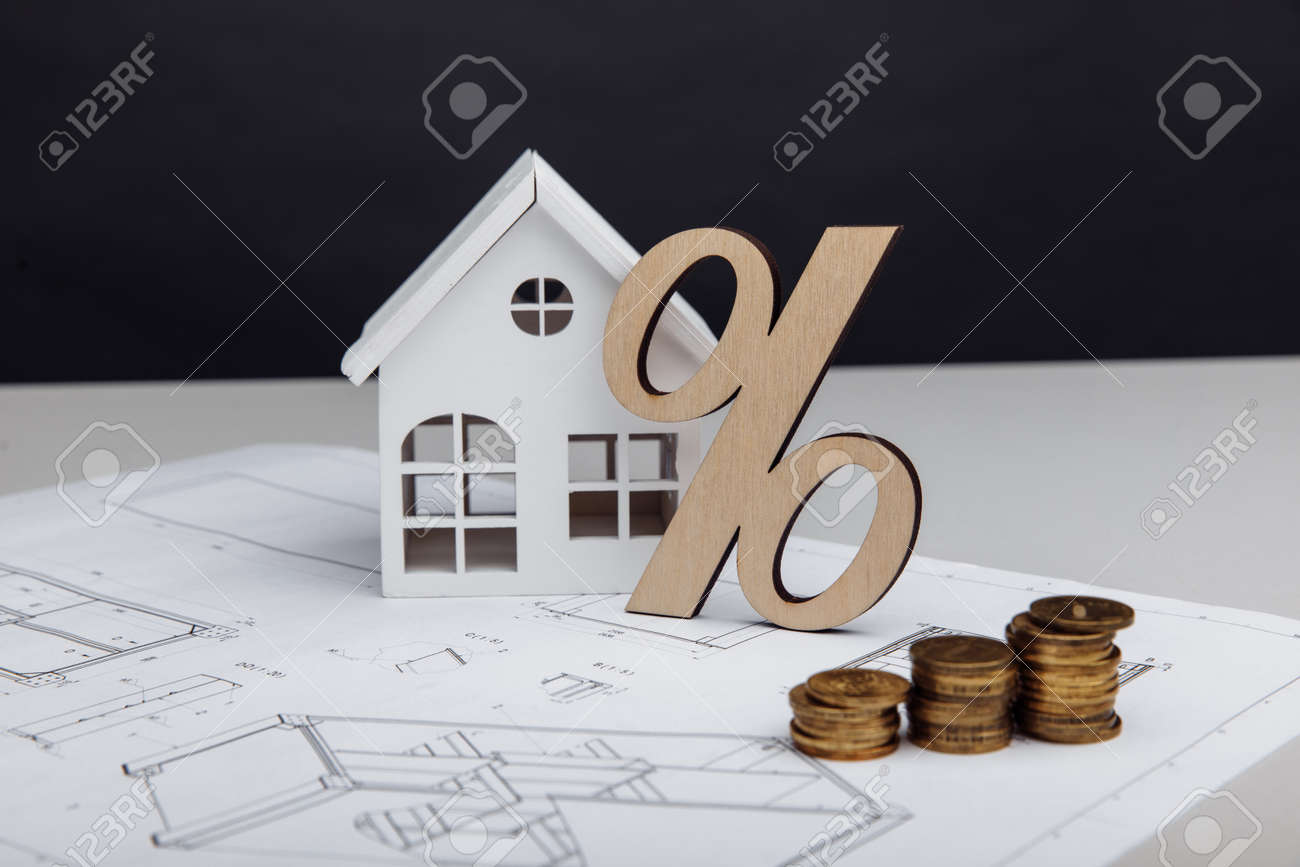 Model of house and symbol of percent with coins on architectural plan. Building investment - 173213427