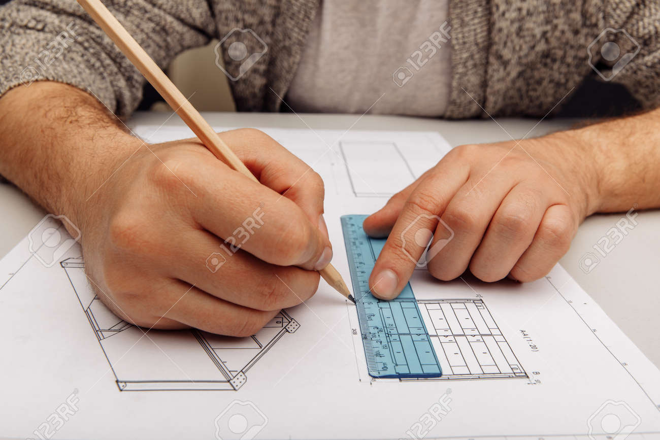 Male engineer works with blueprints laying on a table, using pencil - 173213200