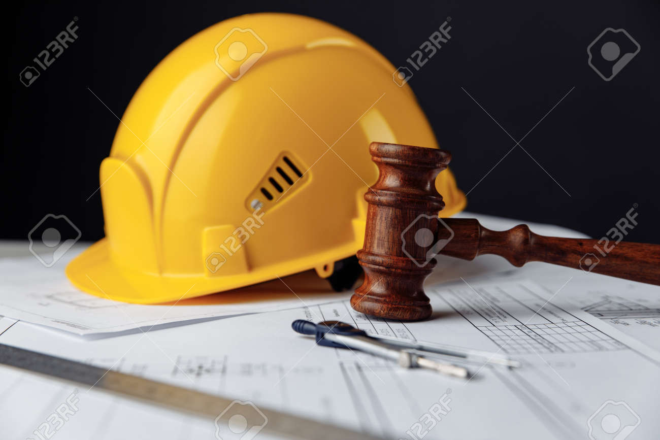 Wooden gavel with yellow helmet. Construction law concept - 173212860