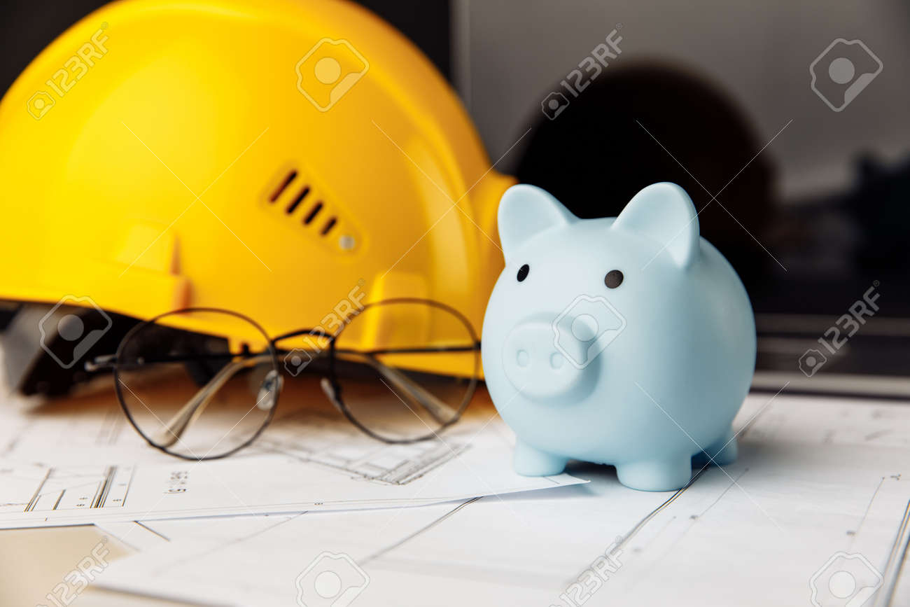 Yellow safety helmet and piggy bank with blueprint, glasses and laptop on table - 173213158