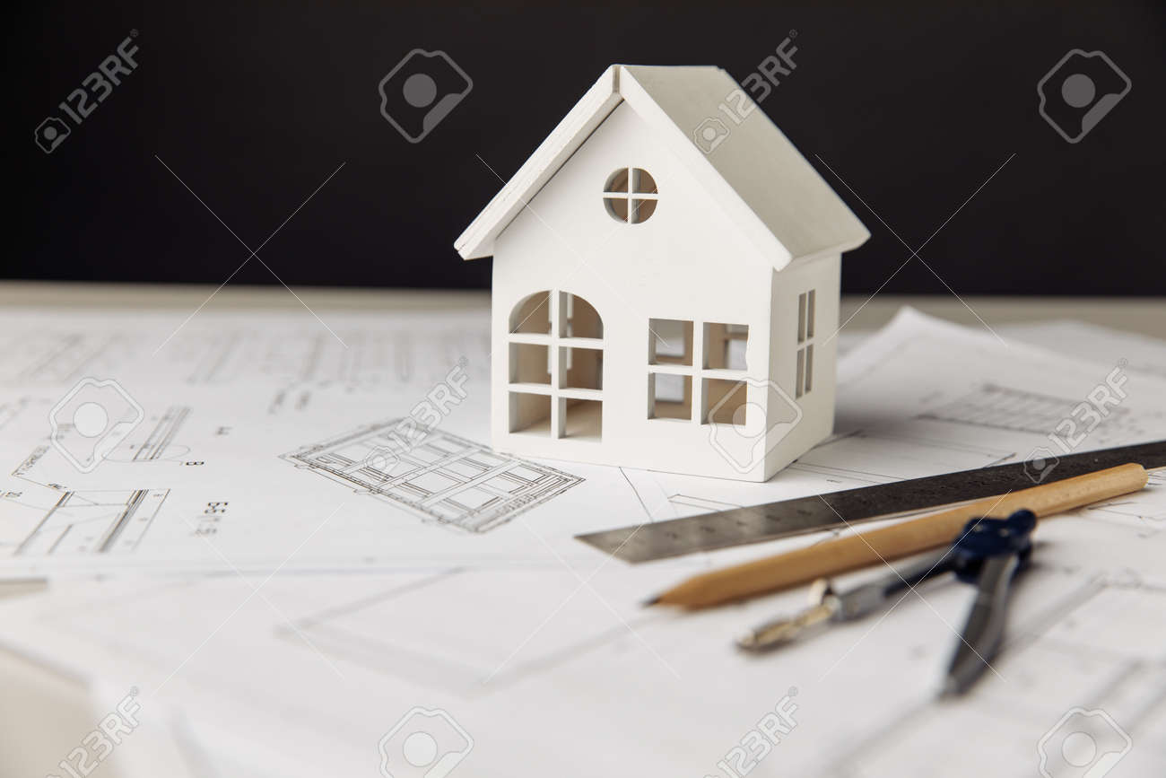 Blueprint with white house, drawing tools and glasses on a table close-up - 173213193