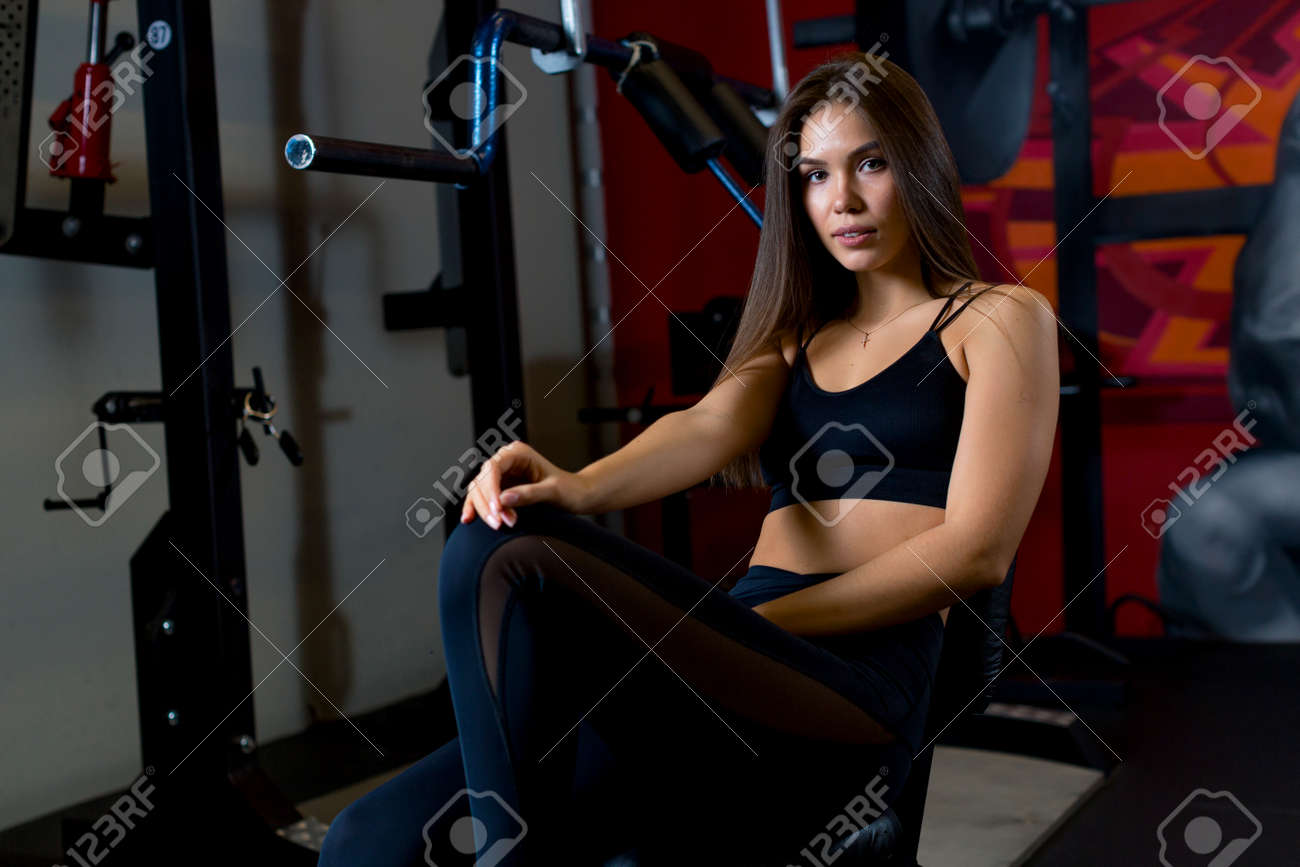 Attractive young girl sits on a simulator in a gym mysteriously staring at the camera. Photo for coaches and gyms. High quality photo - 164116972