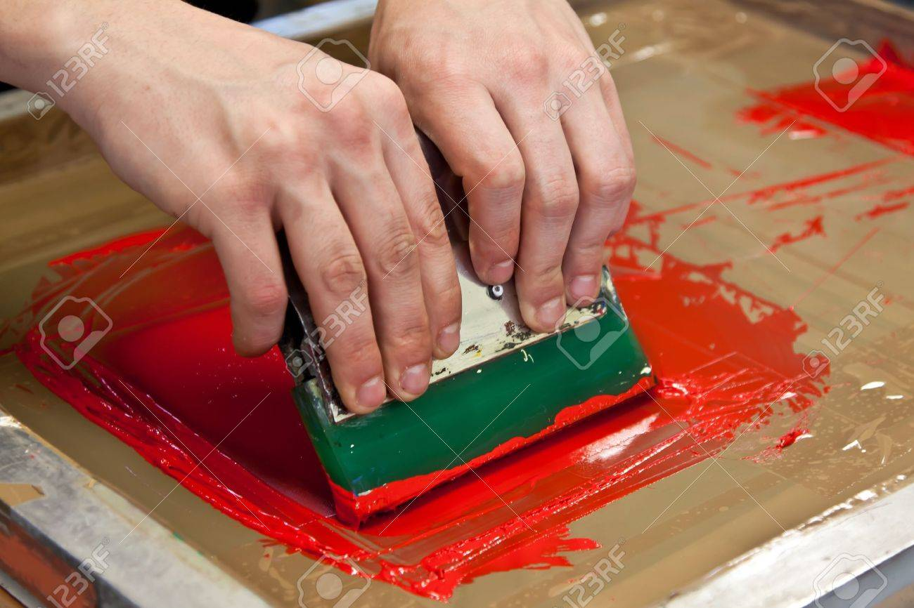 red color is printing on t-shirt with hands pressure Stock Photo - 12818364