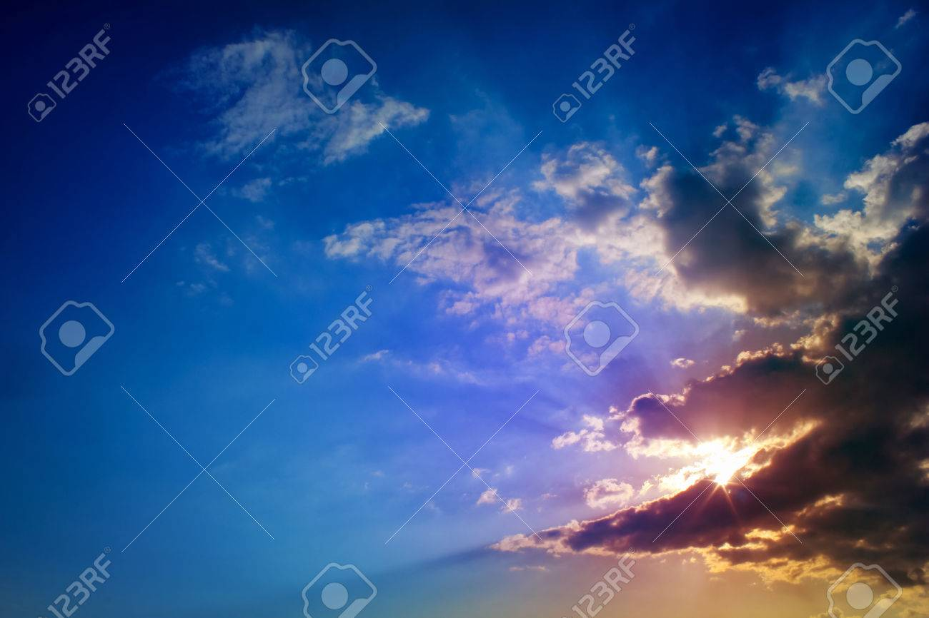 Bright Sun Rays Through The Dark Clouds With Deep Blue Sky Background Creating Beautiful Scenery
