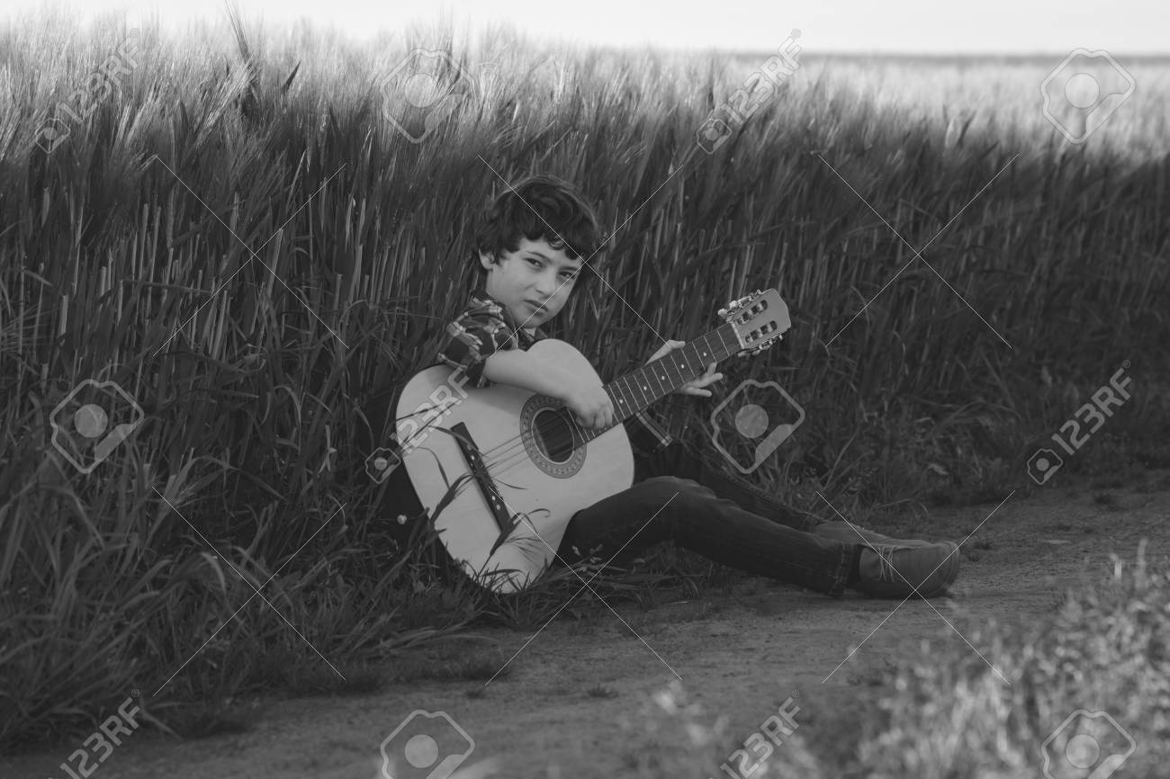A boy in jeans and a shirt is sitting in the field with a guitar. Black and white. Matte stylization. - 99792480