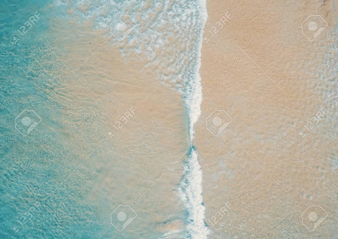 Aerial top view of turquoise ocean wave reaching the coastline. - 136691261