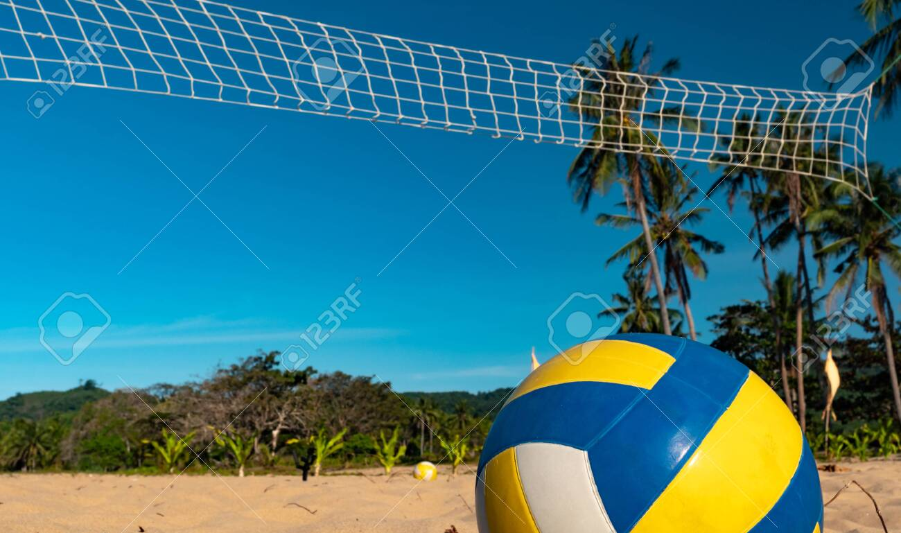 Beach Volleyball. Game ball under sunlight and blue sky with volleyball net on the background - 137868433
