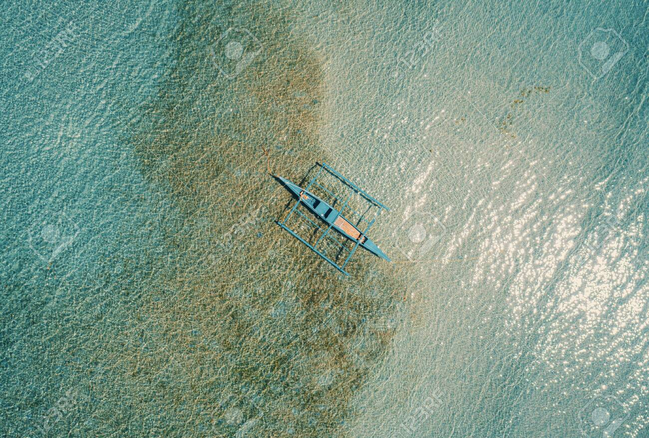 Aerial drone view of boat anchored in the bay with clear and turquoise water. Boat in the tropical lagoon. Tropical landscape. - 137870610