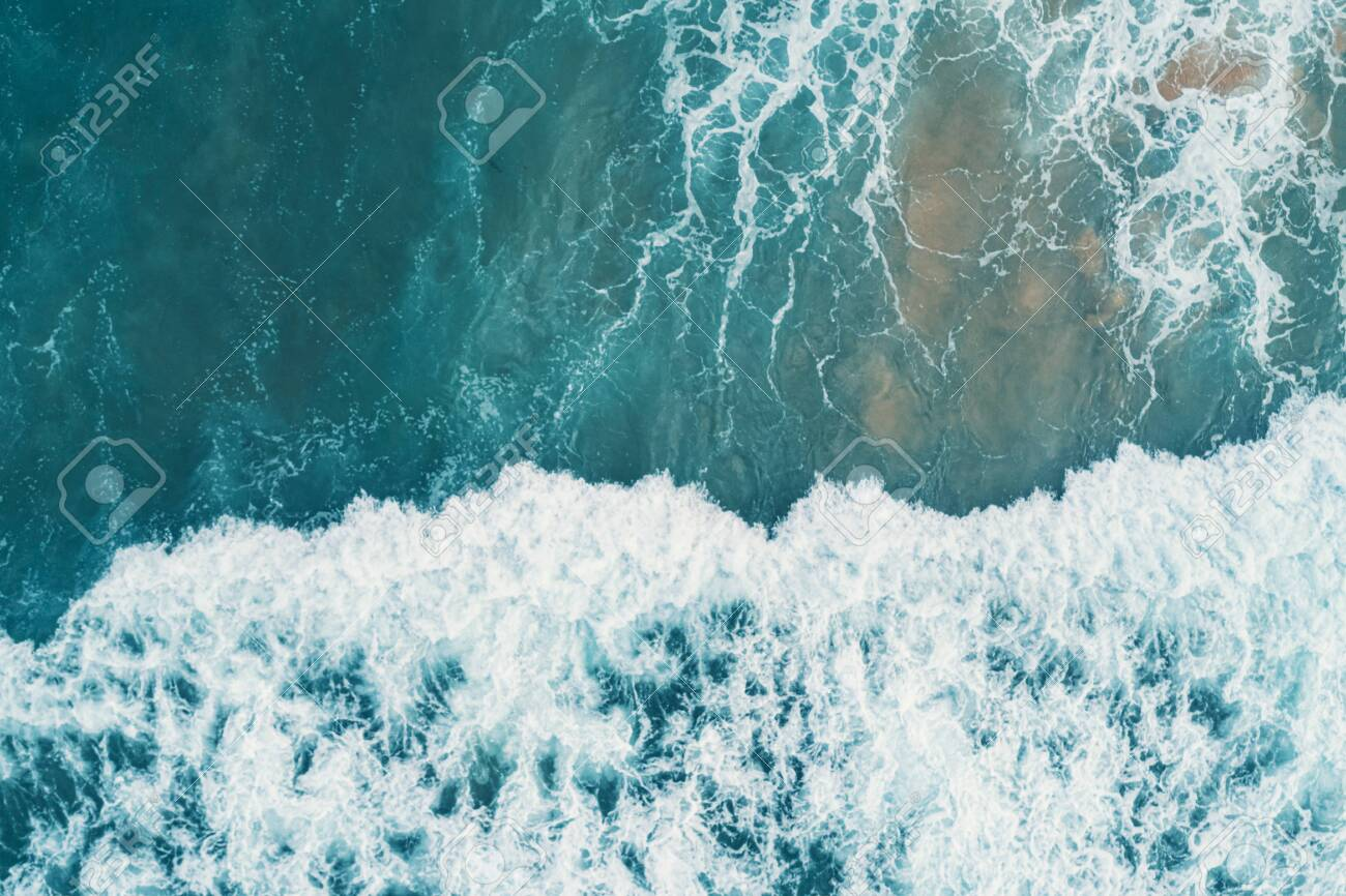 Aerial view of white foam on the surface of the blue sea. - 142934812