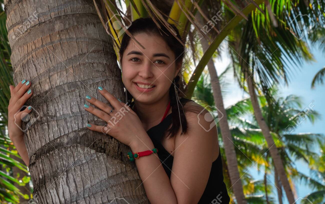 Close-up of cute asian girl hugging palm tree - 142933822