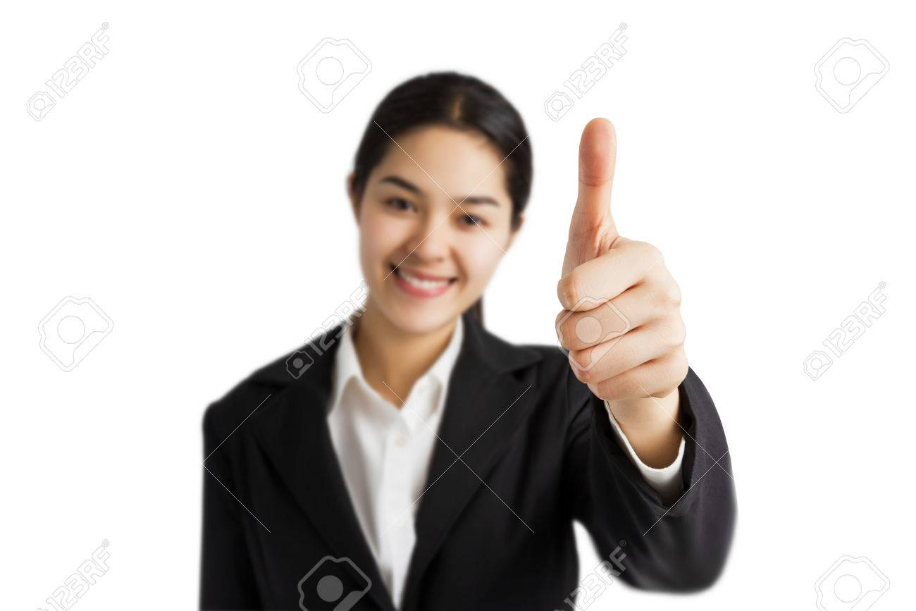 Stock Photo - Young Asian business woman shows thumb up with smiley face  (focus on hand) isolated on white background.