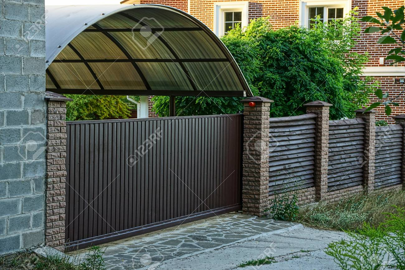 Brown wooden fence and closed gates with a private house near