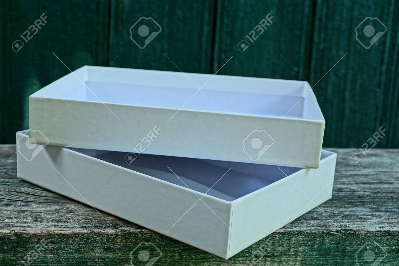 big white open paper box on gray wooden table