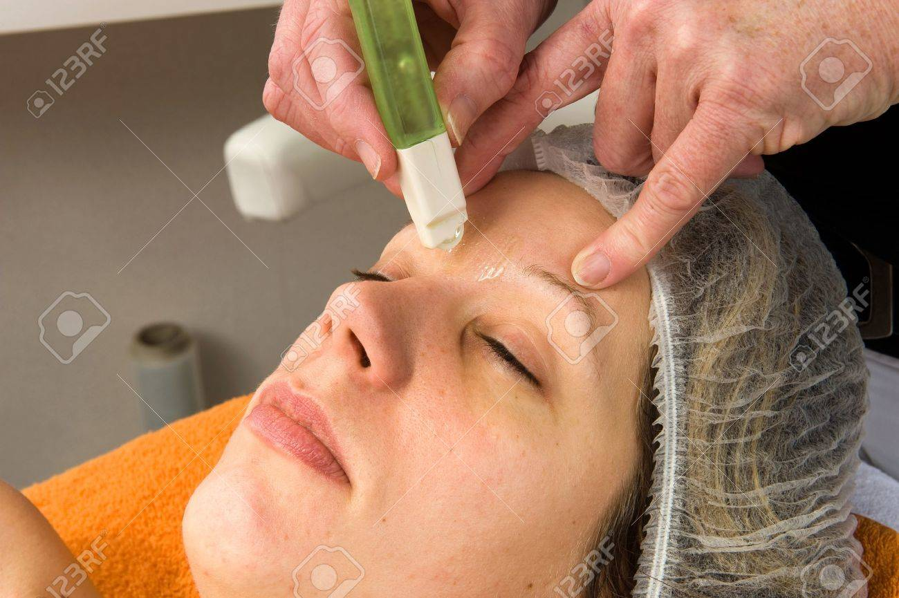 A woman s hair between her eyebrows is being waxed Stock Photo - 17497844