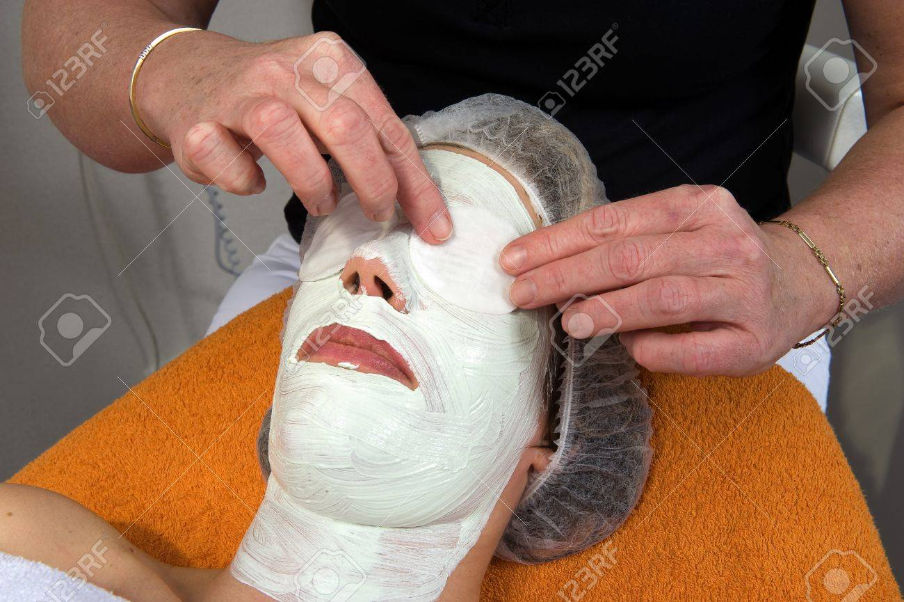 A woman is lying in a beauty salon with a mask on het face while her eyes a covered with wads of cotton wool Stock Photo - 17497851