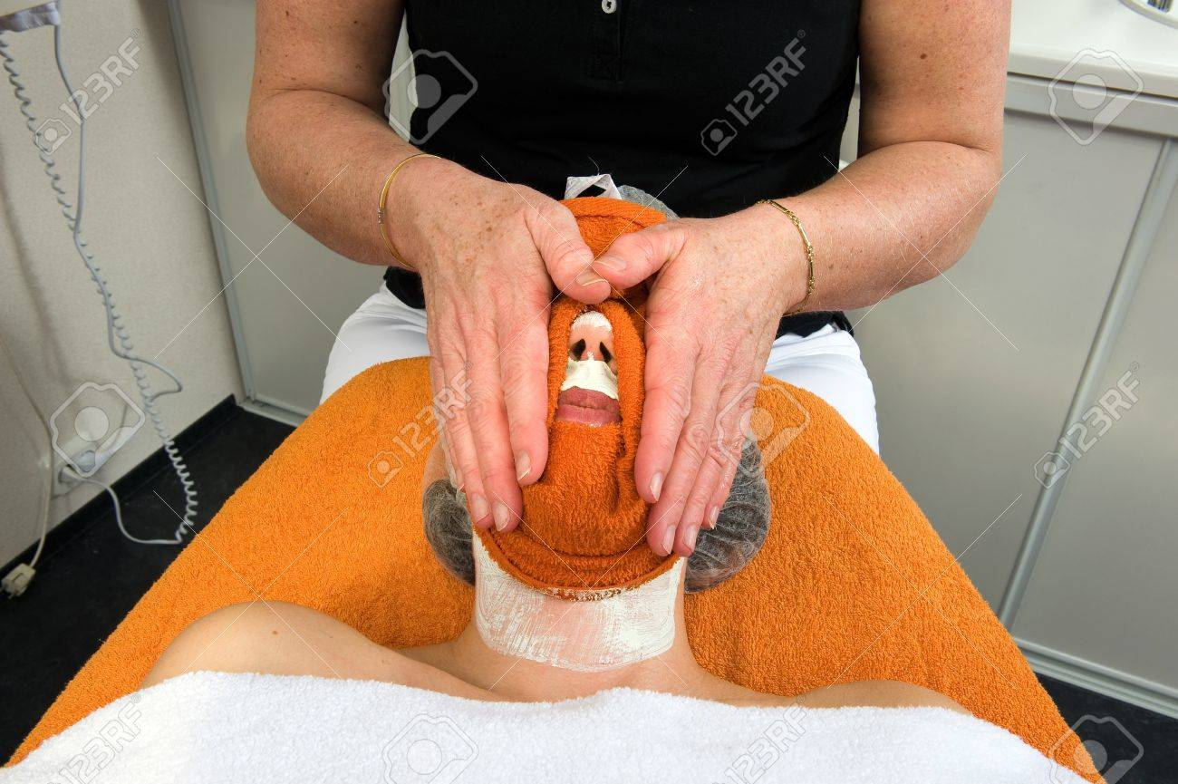 A woman s face is cleaned with a hot towel in a beauty salon Stock Photo - 17497853