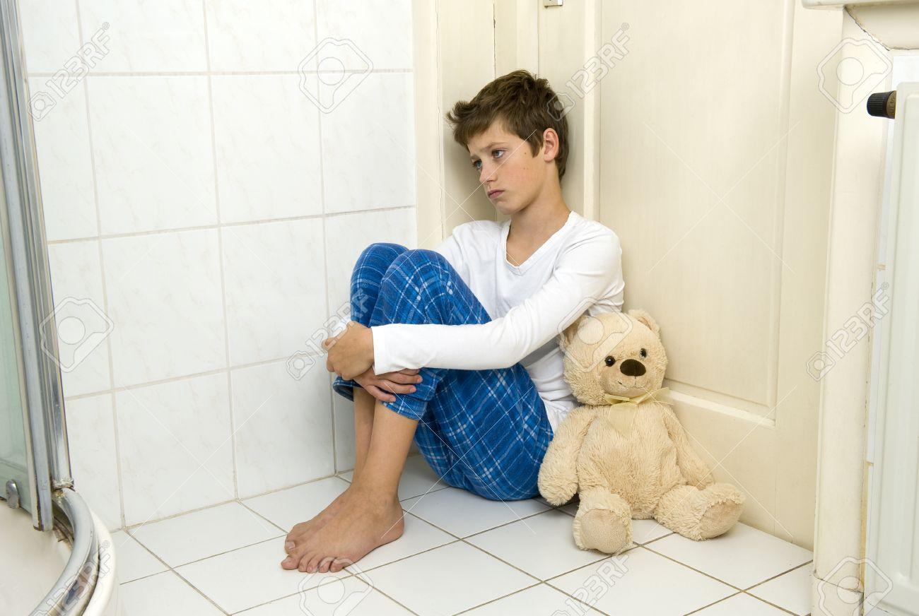 Bagno Con Un Ragazzo : Un giovane ragazzo è seduto paura e depresso in un angolo della