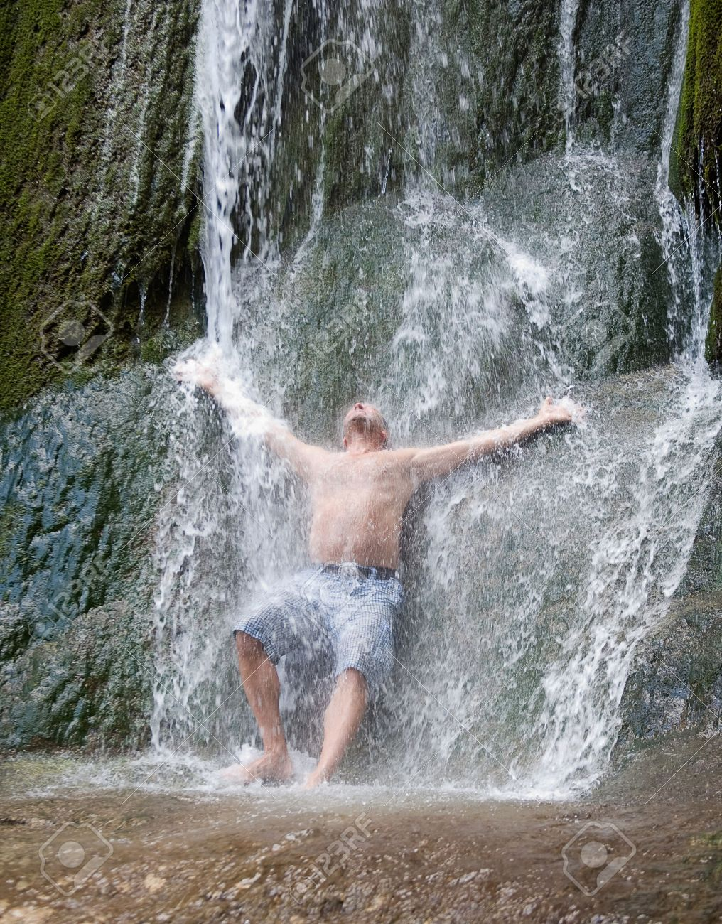 A Man Is Having Shower Underneath Natural Waterfall Stock Photo