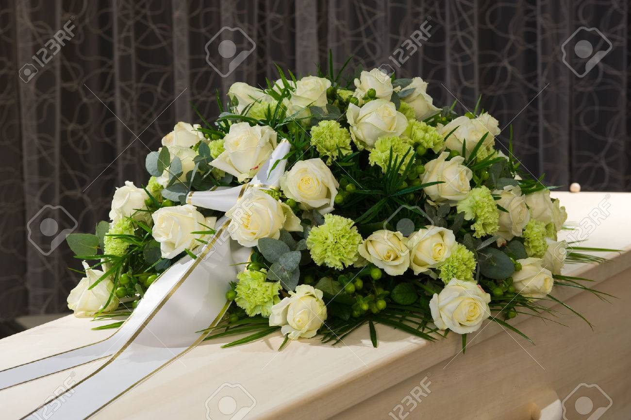 A coffin with a flower arrangement in a morgue - 52023244