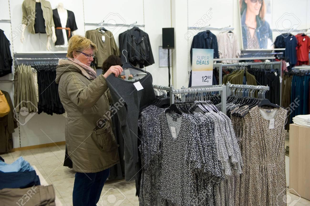 En liquidación diseño atemporal comprar ENSCHEDE, LOS PAÍSES BAJOS - 13 DE ABRIL DE 2017: Una mujer está haciendo  compras en la tienda de ropa C & A después de que se haya vuelto a abrir.