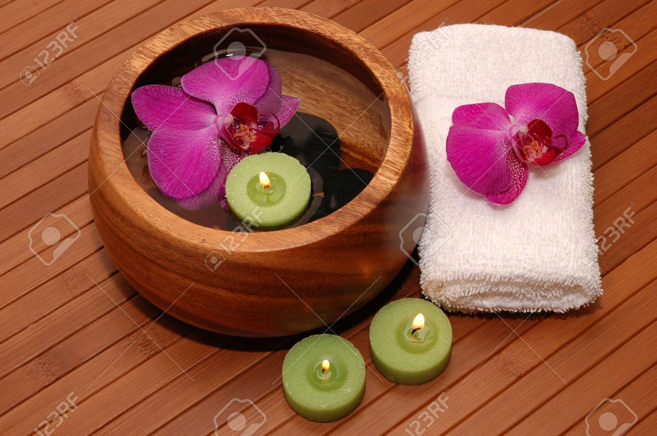 Floating green candles, orchids, towels on a bamboo mat Stock Photo - 672811