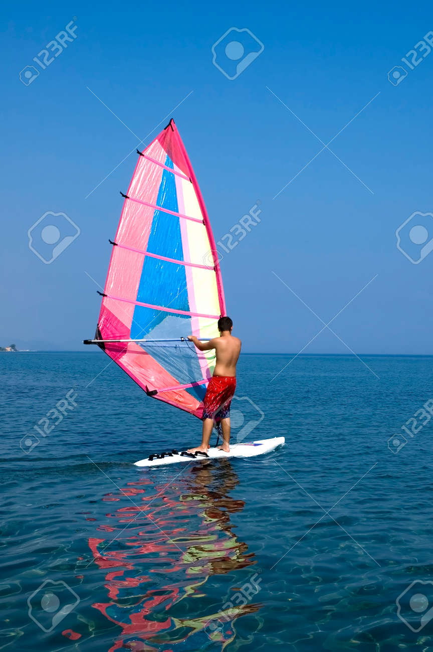 A Teenage Surfer Surfing In Mediterranean Sea On A Not Very Windy
