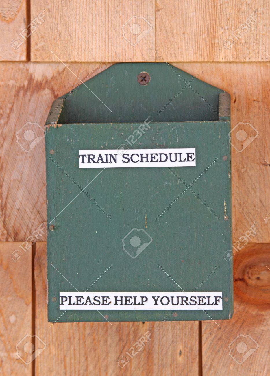 An empty train schedule holder screwed to cedar shingle siding. Stock Photo - 5299178