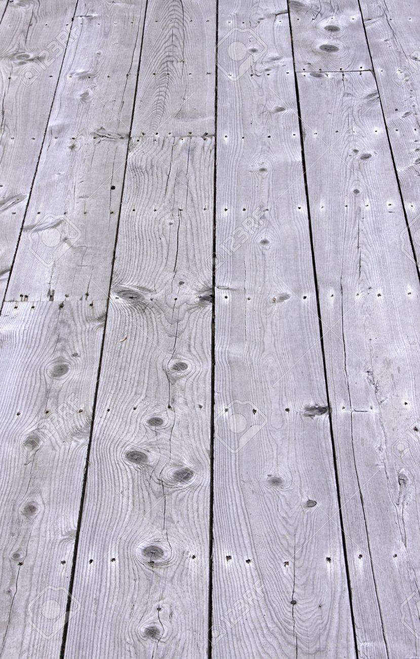 several rows of weathered deck boards with gaps showing stock photo
