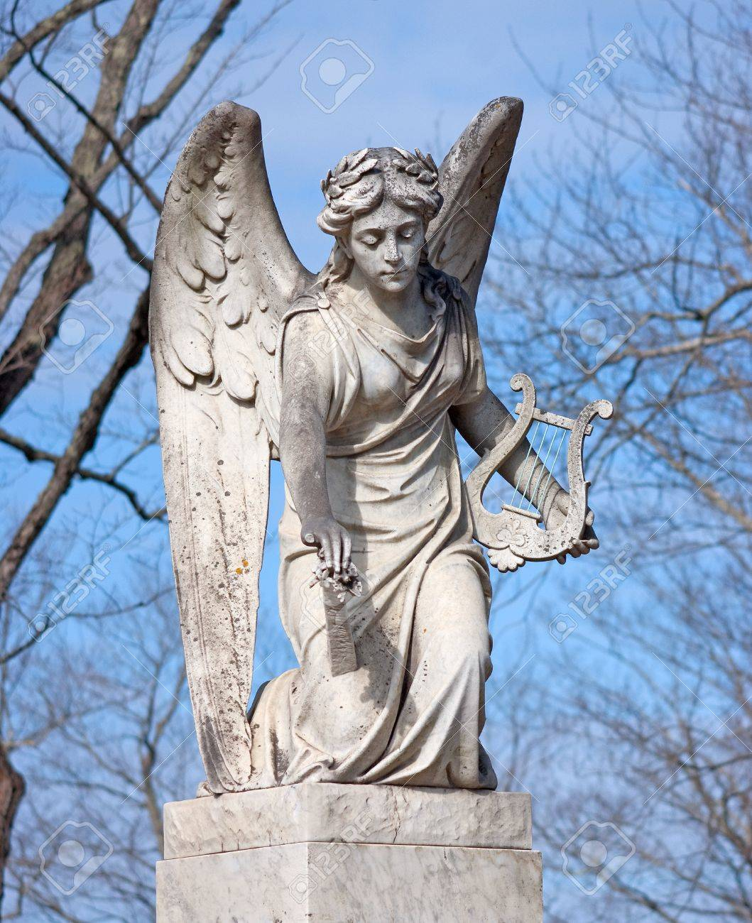 an aged statue of an angel holding a harp stock photo picture