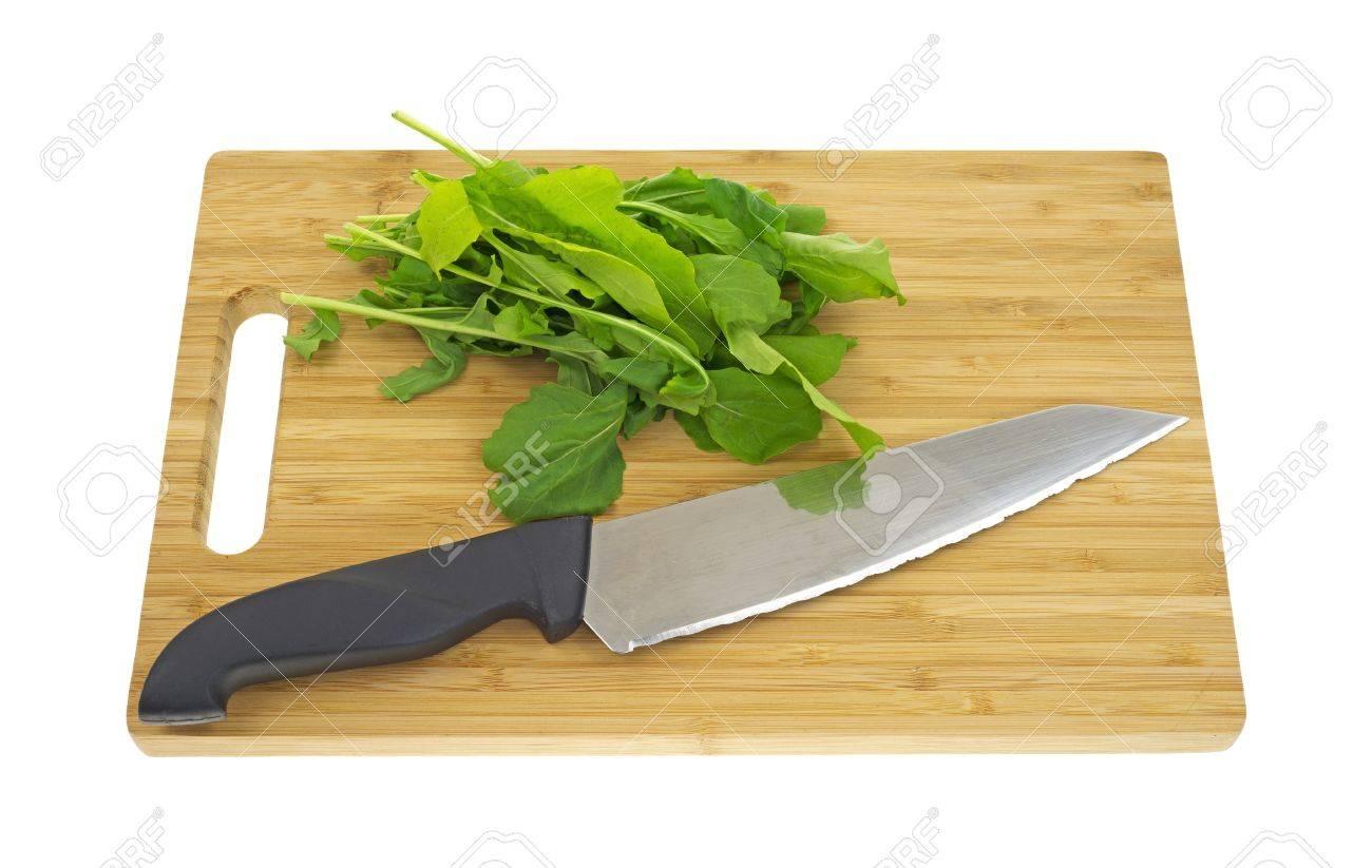 Unas Hojas De Rúcula Una Tabla Para Cortar Madera Con Un Cuchillo ...