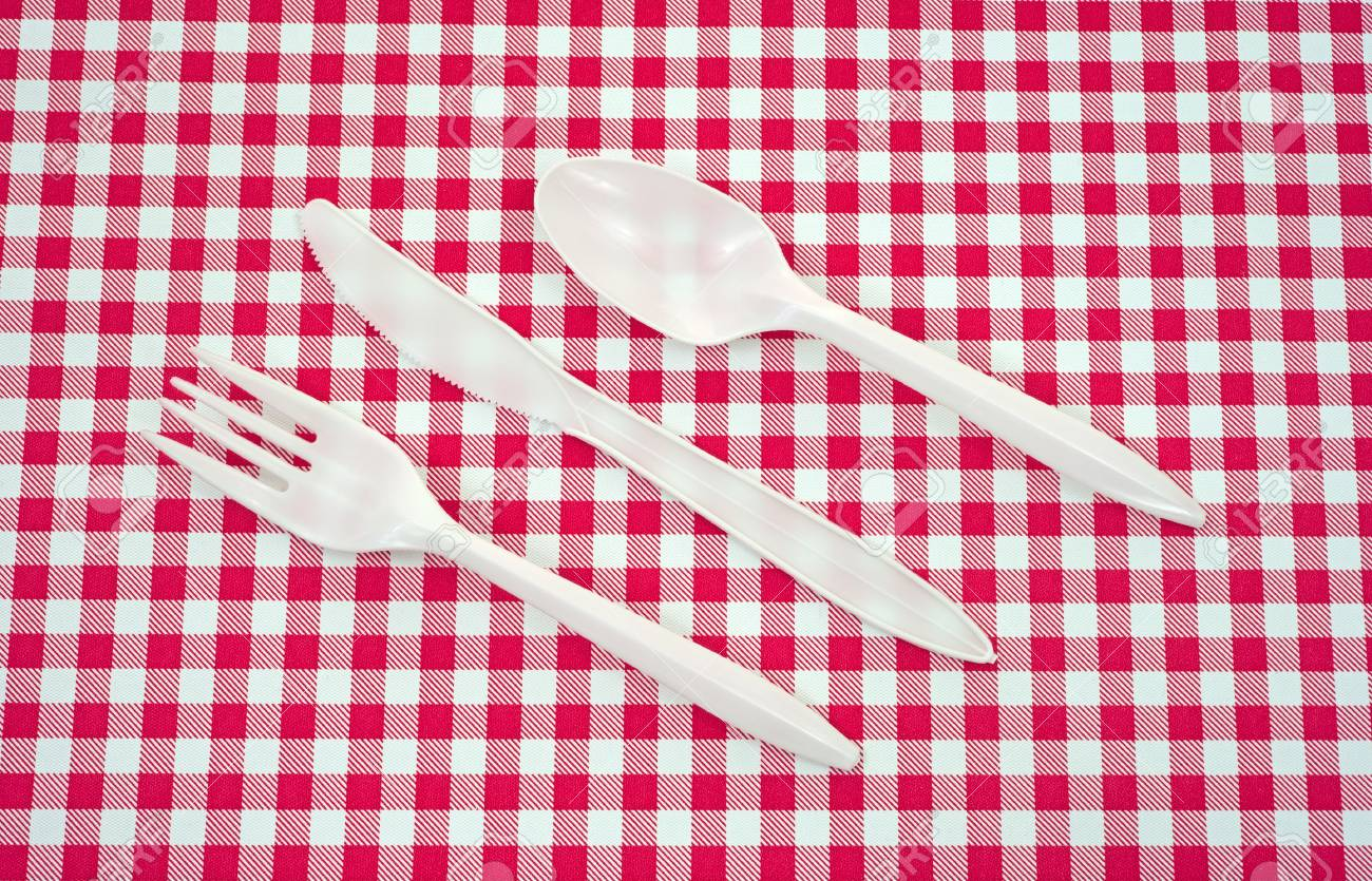 A Set Of Plastic Silverware Arranged On A Red And White Picnic Tablecloth.  Stock Photo
