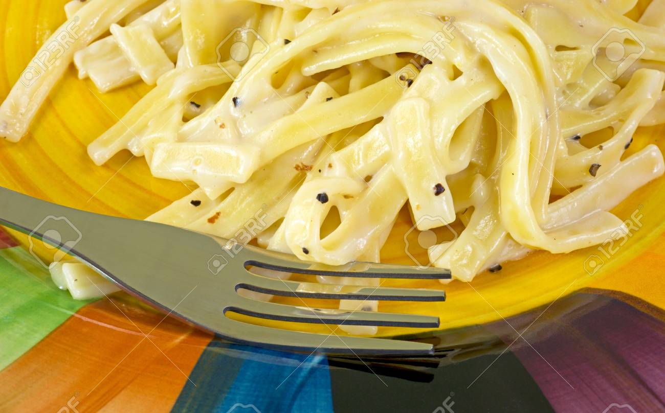 Close view of a serving of Fettuccine Alfredo on a colorful plate with fork Stock Photo - 16333240