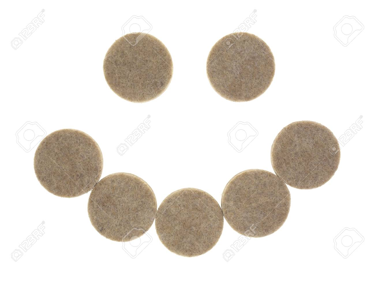 A group of felt surface protectors for protecting furniture and flooring in the shape of a smile on a white background. Stock Photo - 20407821