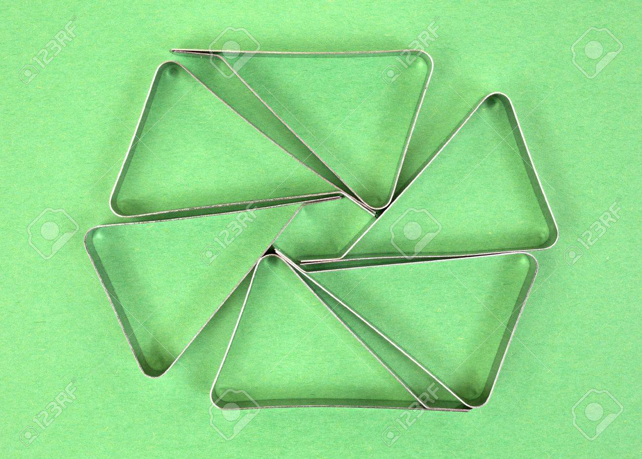 Several stainless steel tablecloth clamps used for keeping tablecloths from blowing from picnic tables on a green background. Stock Photo - 20721412