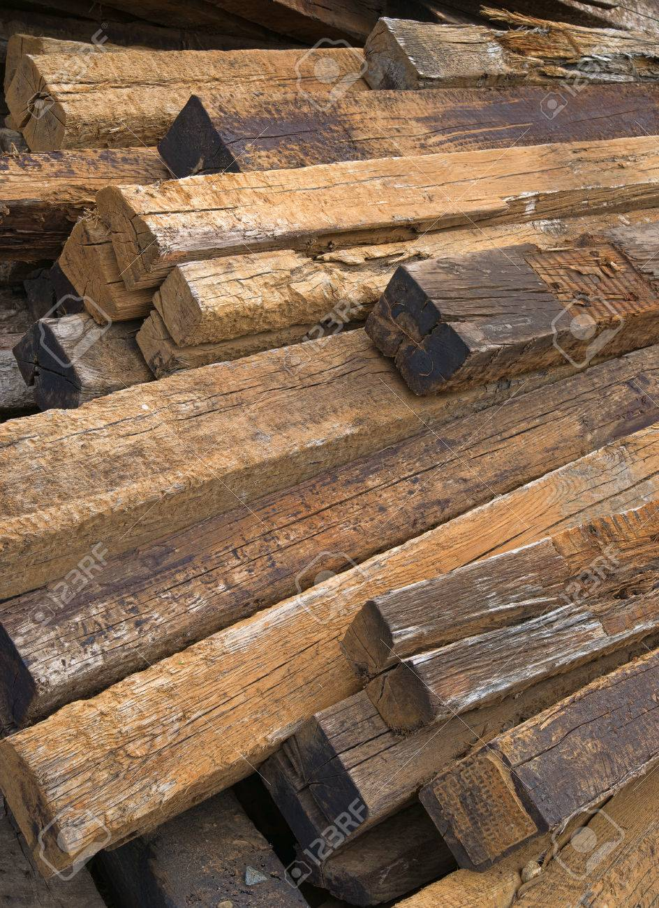 A large pile of used railroad ties left to rot outdoors
