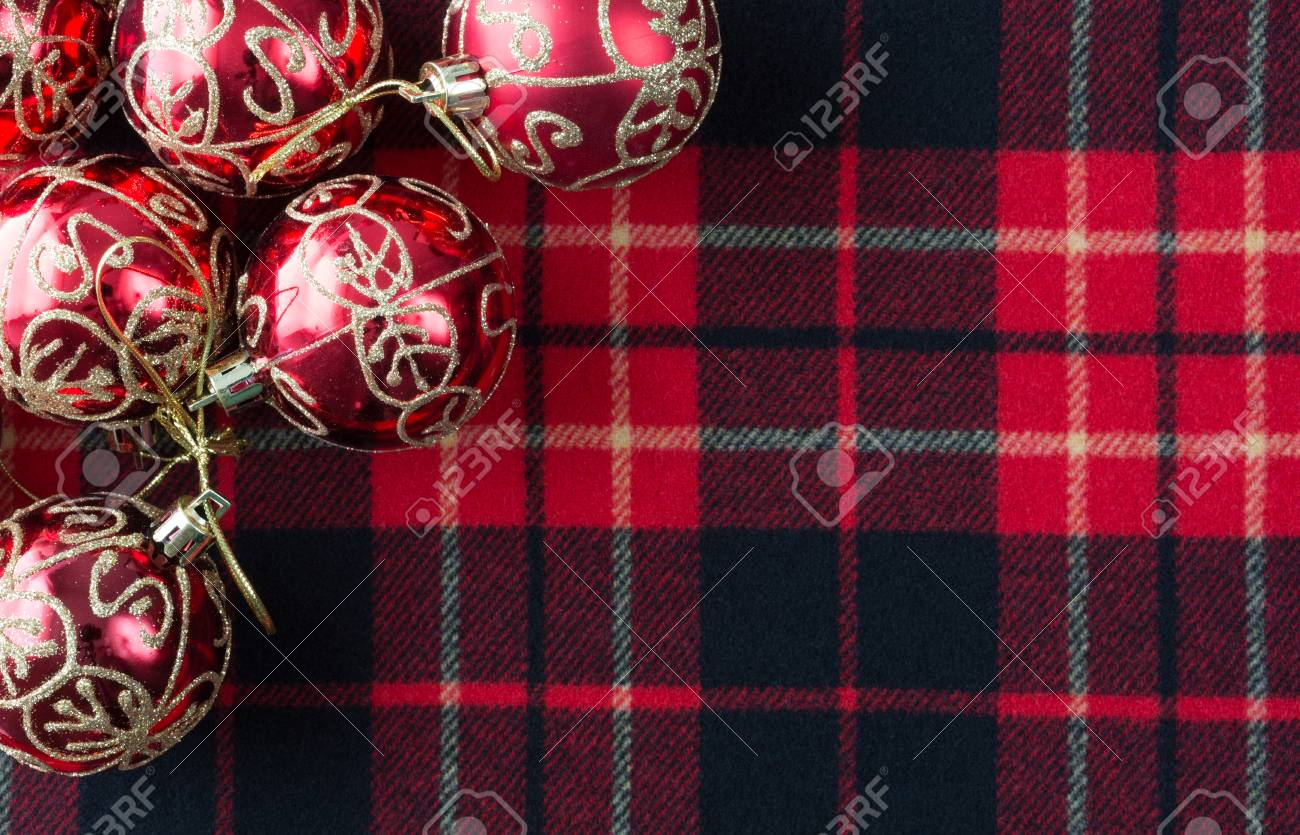 stock photo top view of several christmas ornaments atop a red black and white tartan cloth with room for a message