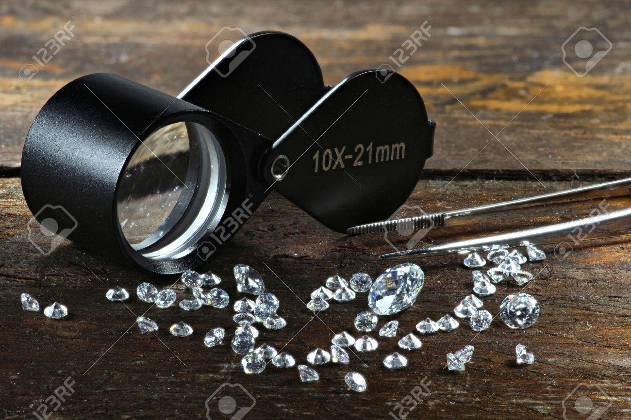 cut diamonds with folding magnifier and tweezers on wooden background - 50537567