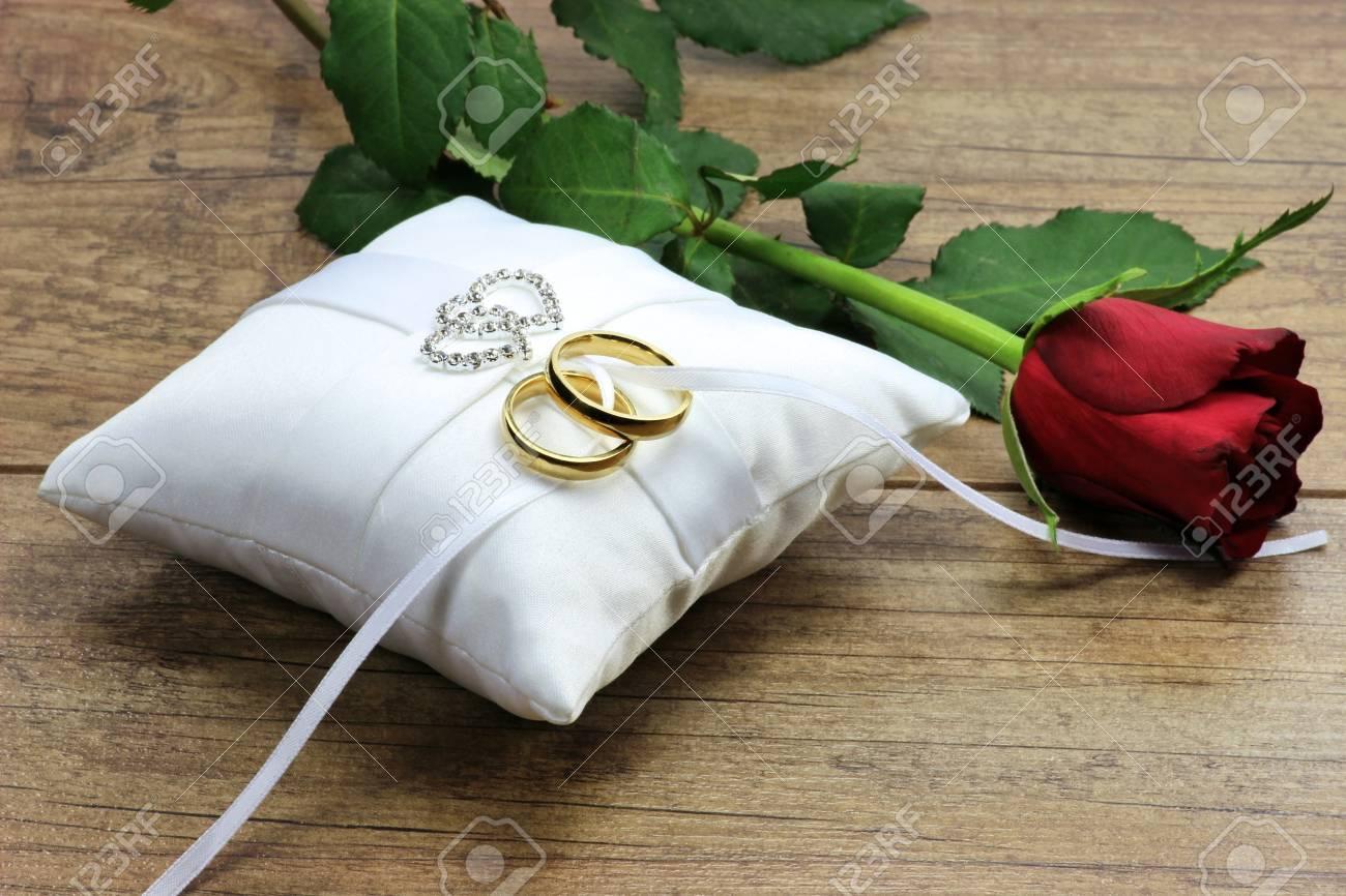 Golden wedding rings on white ringbearer pillow - 51171703