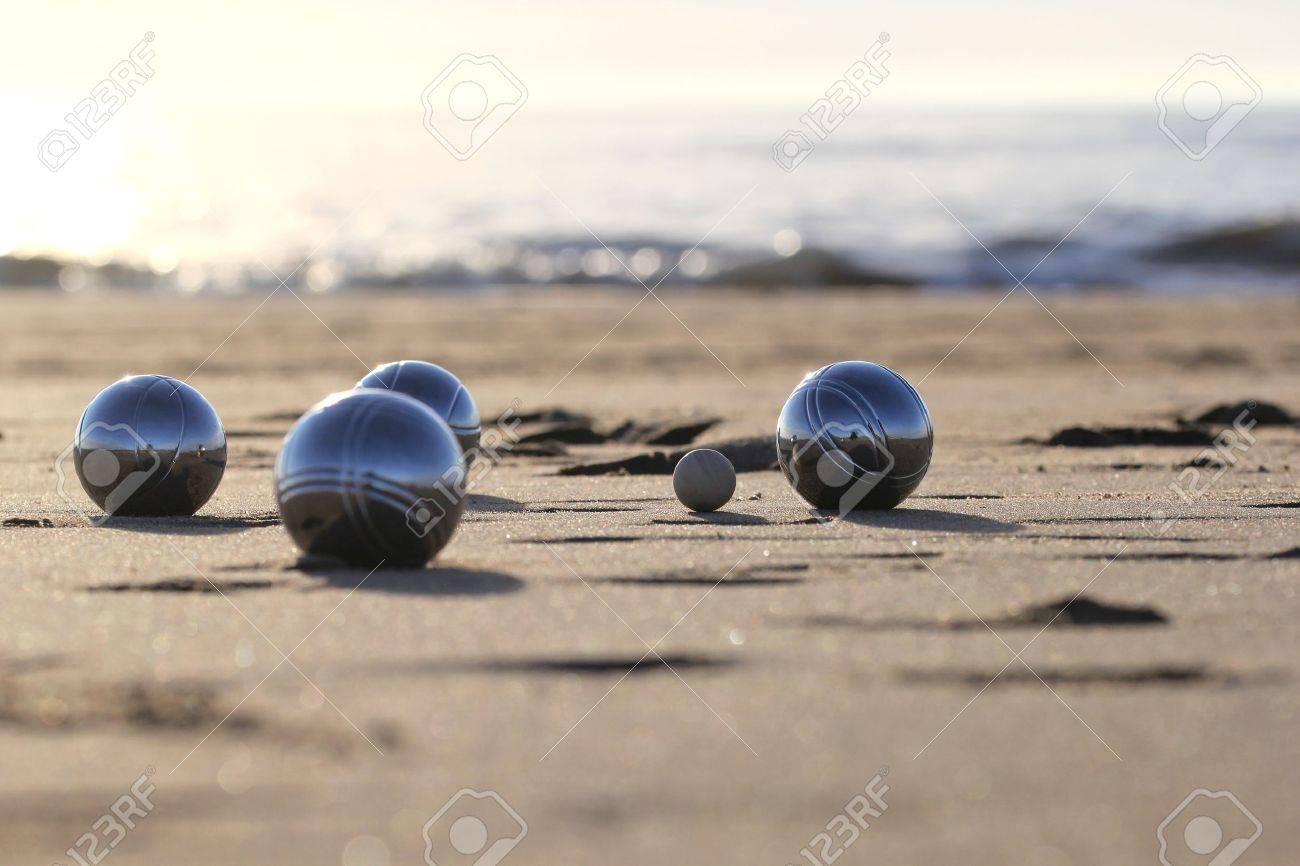 bocce balls on sandy beach - 51783336