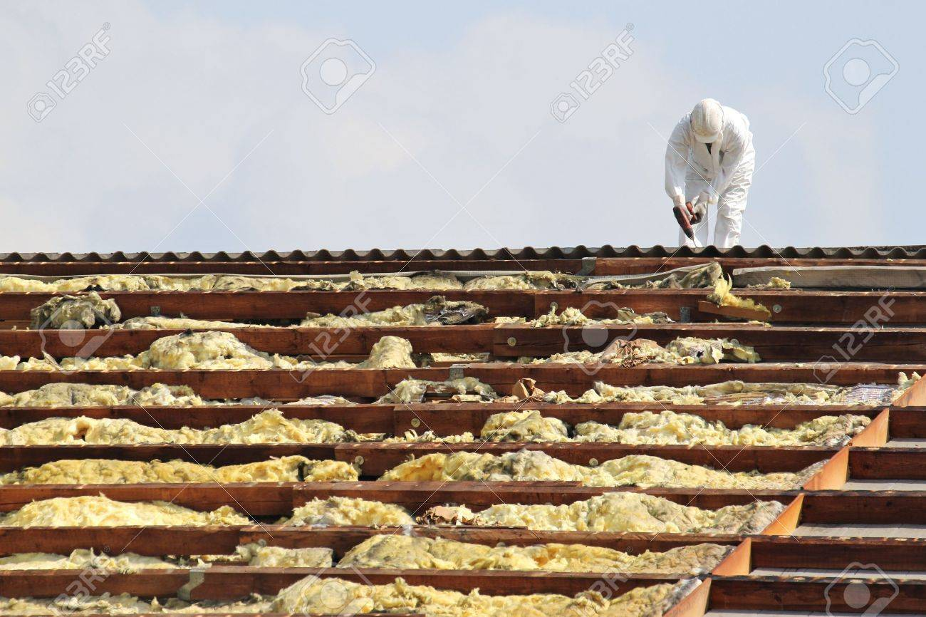 workman at rooftop of building being remediated - 52074795