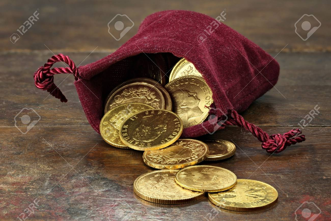 various European circulation gold coins from the 19th / 20th century in a velvet purse on rustic wooden background - 68965213