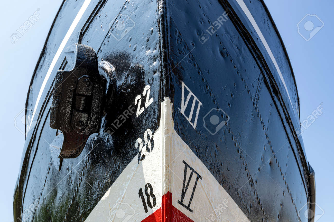 metric and imperial draft marks on the bow of an old ship with reveted hull - 172227124