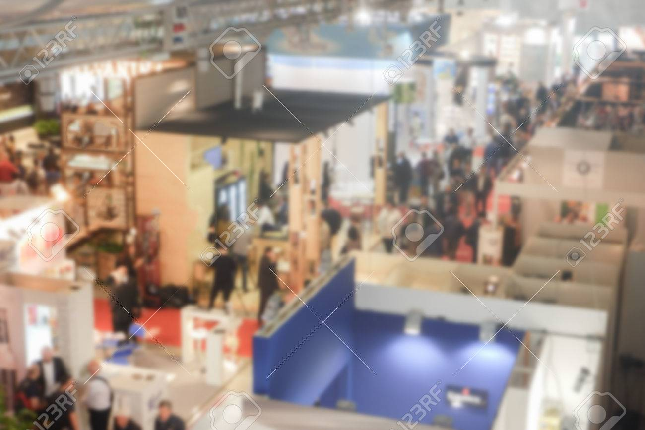 Defocused background of a trade show with people visiting the commercial exhibition. Intentionally blurred post production for bokeh effect Banque d'images - 58923466