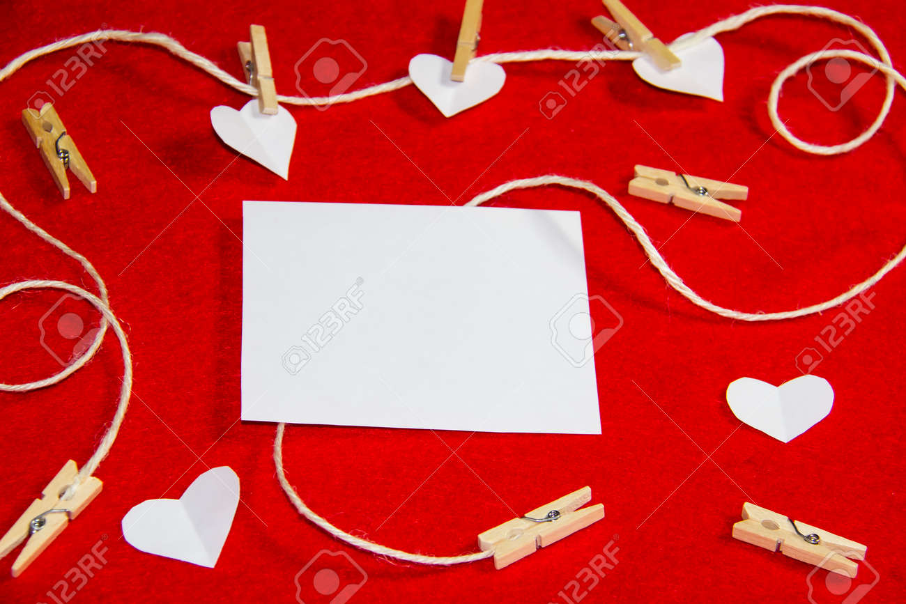 A red background from felt. A composition from heart, thread and clothespins. Background with place for write for valentines day and christmas. - 148565232